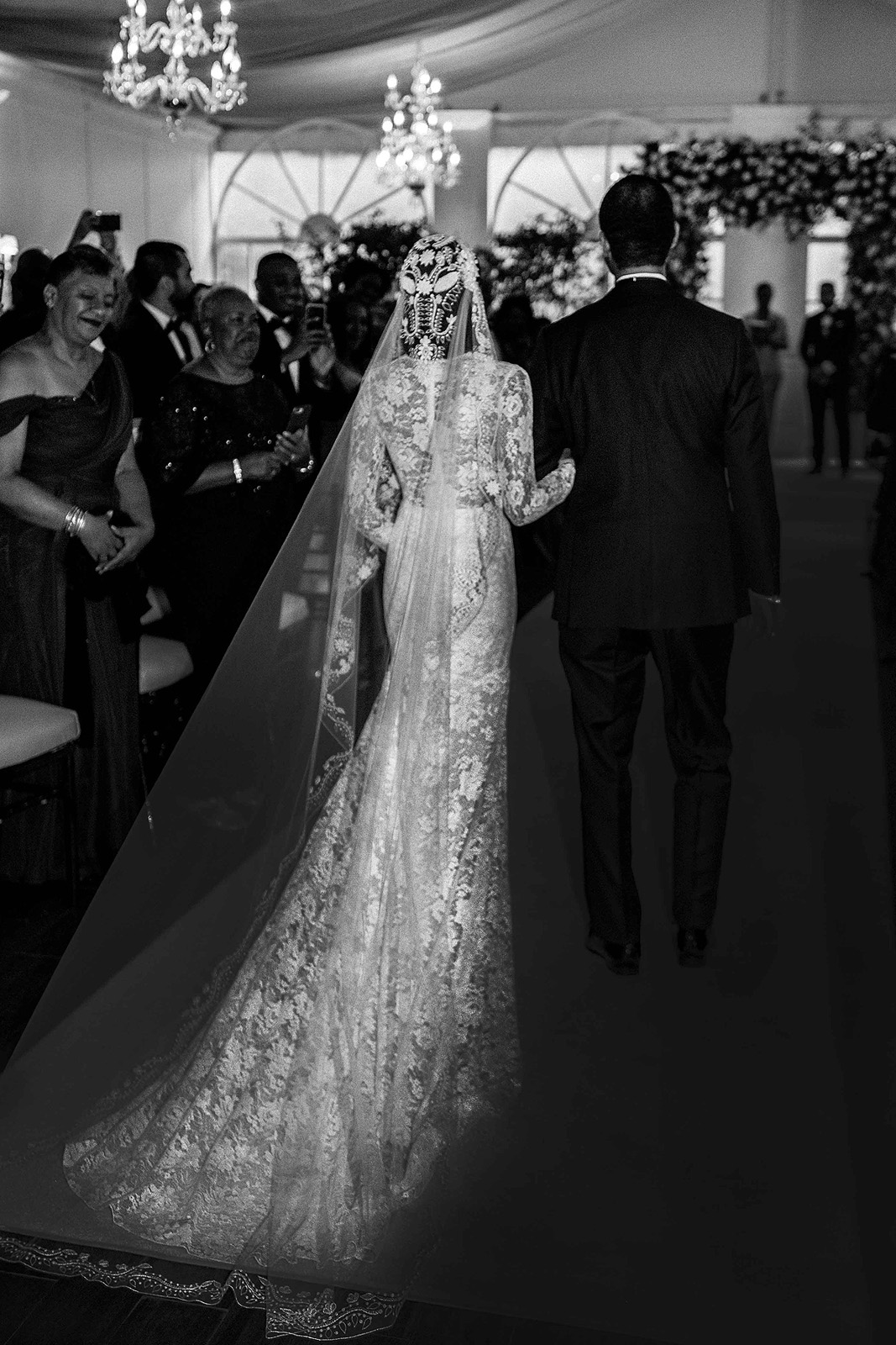 bride walking down aisle in long lace veil